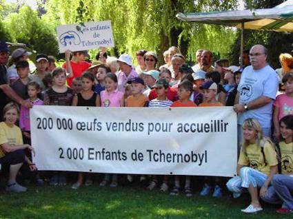 Des enfants et des responsables de l'association tiennent une banderole.
