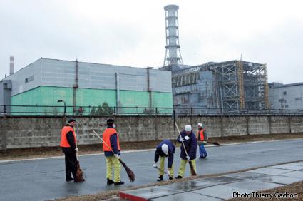 Photo d'ouvriers nettoyant les abords de la centrale.