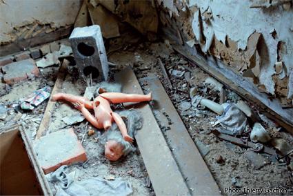 Photo d'une poupée cassée dans une maison abandonnée.