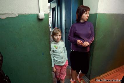 Photo de Katia et sa maman sur le seuil de la porte de leur logement.