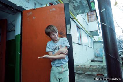 Photo de Serguei, 10 ans, faisant signe de rentrer dans son HLM.