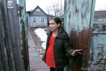 Photo d'Anasthasia, enceinte, devant l'entrée de son jardin.