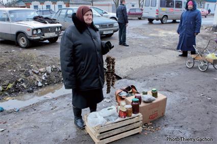 Photo d'une personne agée vendant des champignons et des confitures sur un marché.